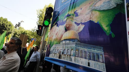 A man stands by a billboard with a picture of the world and Jerusalem's Dome of the Rock, as Iranians march in a Qods (Jerusalem) Day rally, an annual anti-Israel event, in Tehran, Iran, on July 10, 2015.